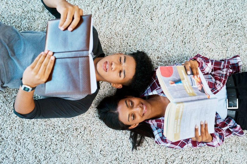 Man and woman laying on carpet reading books together
