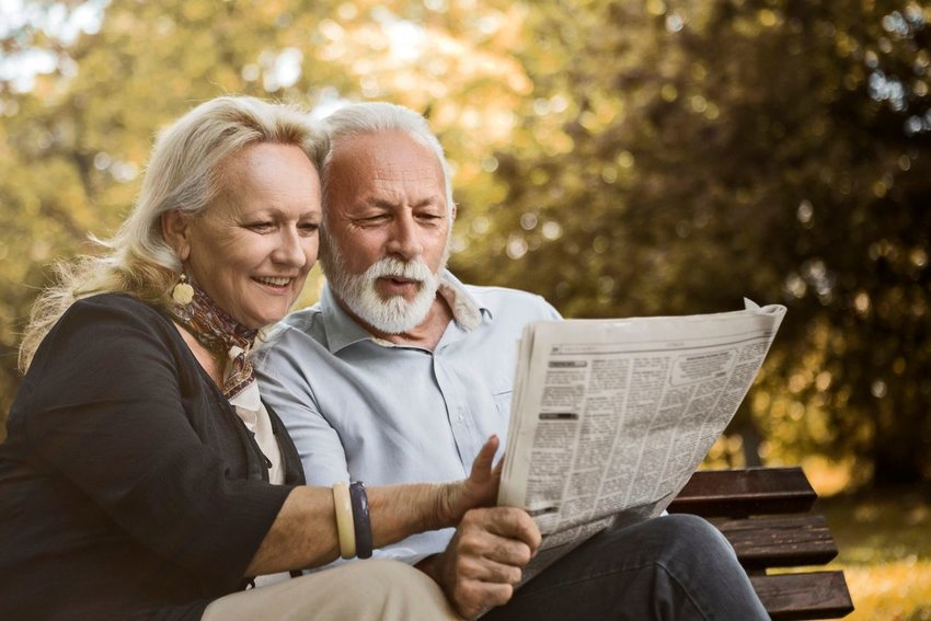 Couple sits on a park bench while reading the newspaper outside