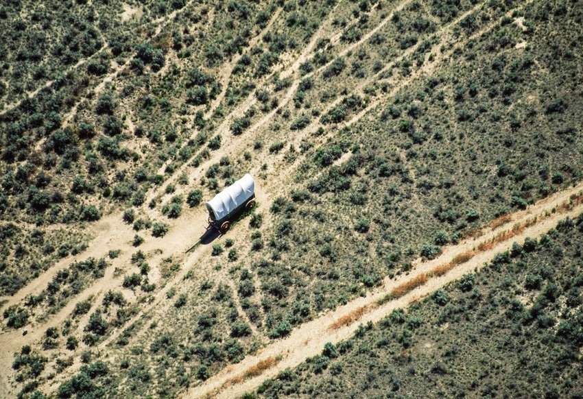 Aerial view of covered wagon on a dusty Oregon Trail road
