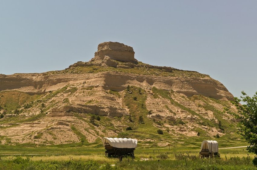 Covered wagons move across the plains with large rocky hills in the background