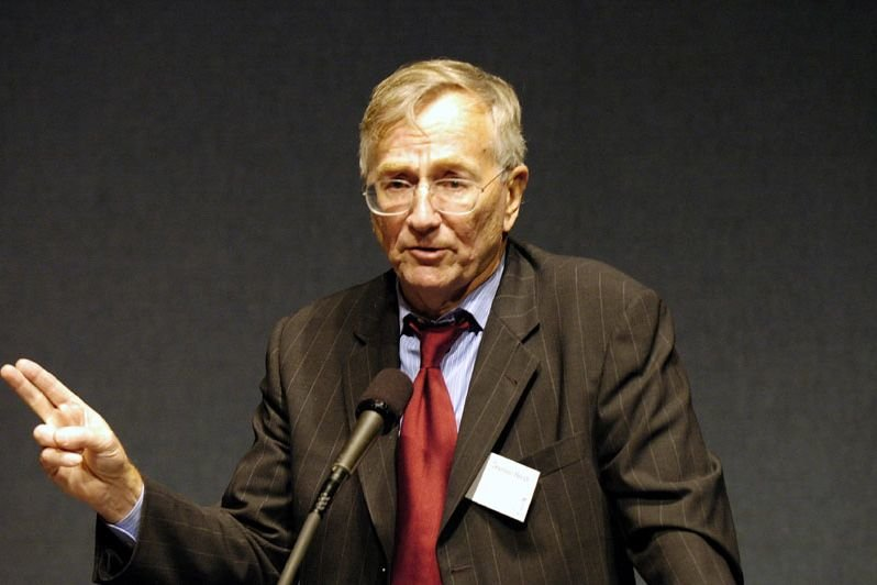 Photo of Seymour Hersh standing behind a microphone