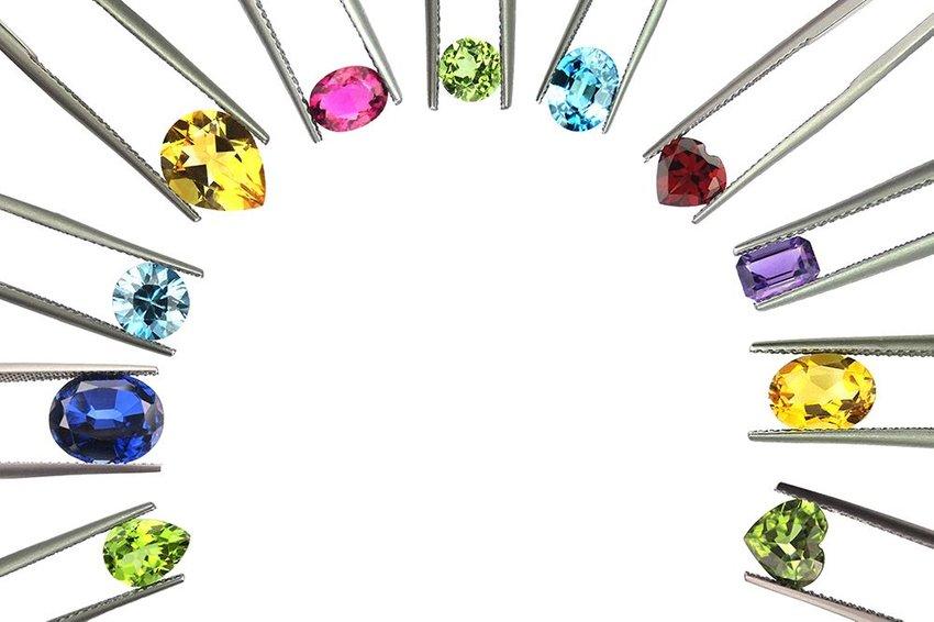 Various gemstones of different colors each held by tweezers in a half moon design