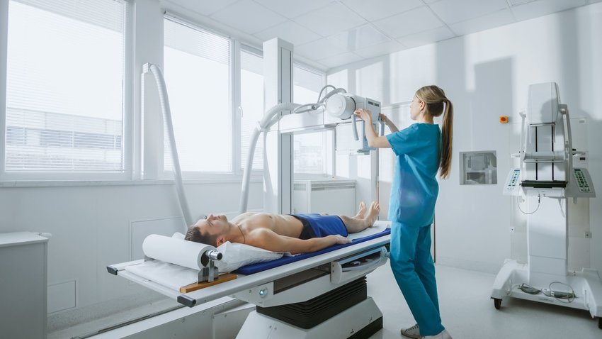 Medical technician and patient interacting with X-ray diagnostic machine in hospital