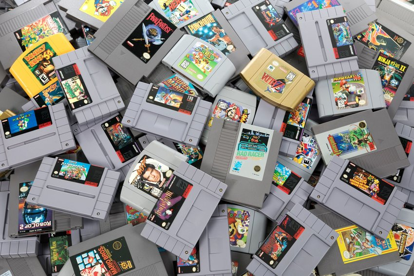 Overflowing pile of classic Nintendo game cartridges from the 90s