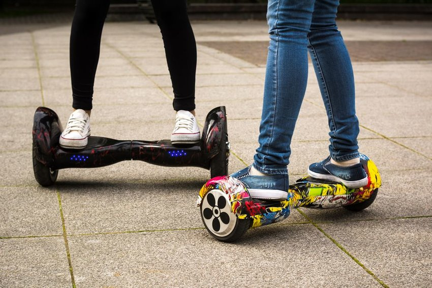 """Young people ride two-wheeled """"hoverboard"""" toys in white sneakers and jeans"""