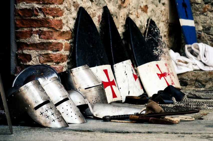Medieval weapons, shields and helmets from crusade era lined up against brick wall