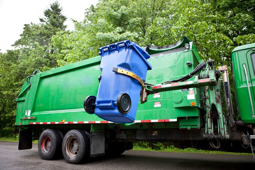 Green refuse truck lifts a blue recycling bin for trash collection in a residential neighborhood