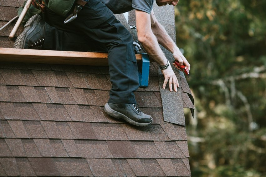 Roofer replacing black shingles while standing on a deeply slanted rooftop