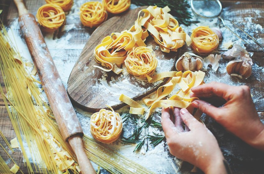 Up close view of hands preparing and forming raw pasta noodles