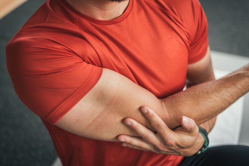 Man in red shirt holds elbow and stretches shoulder joint during workout