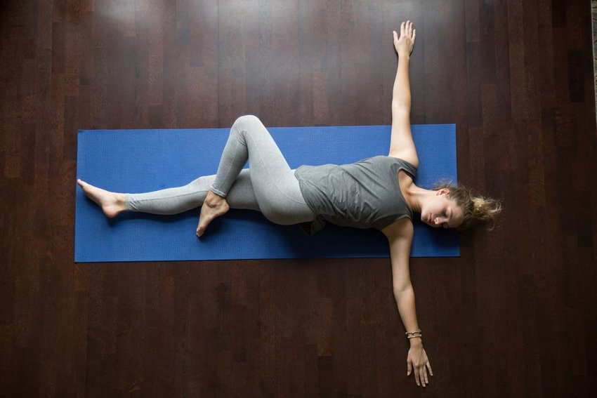 Woman laying on a blue yoga mat performing a mobility spinal stretch