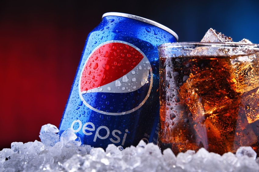 Up close view of Pepsi can and ice-filled glass against a blue and red backgrond