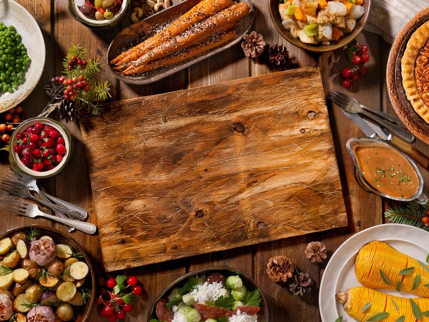Thanksgiving table with wooden cutting board and variety of dishes ready for serving
