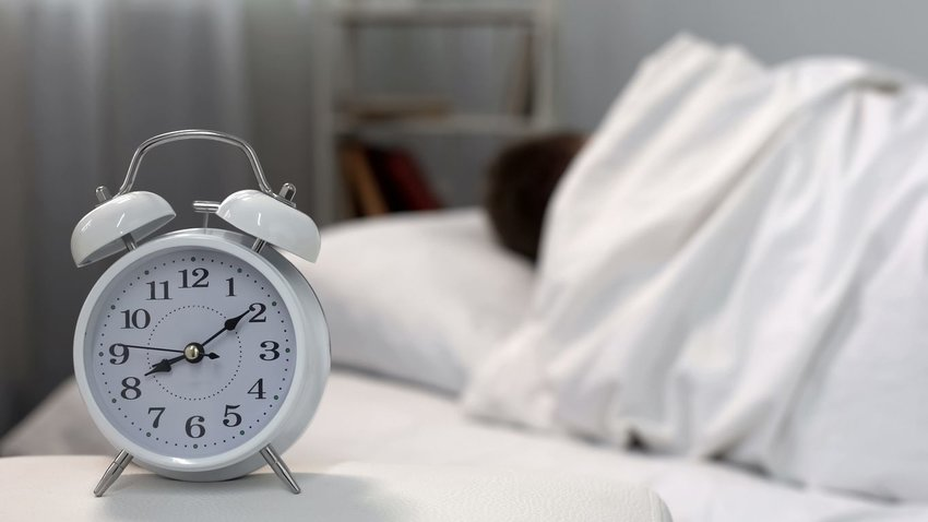 Person sleeping under white sheets with alarm clocking ticking in foreground