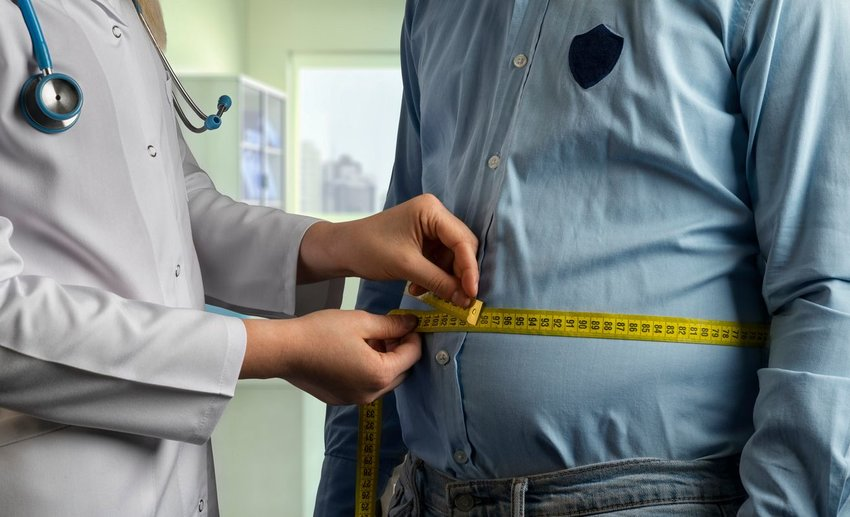 Doctor pulling tape measure around patient's waist to estimate body fat levels