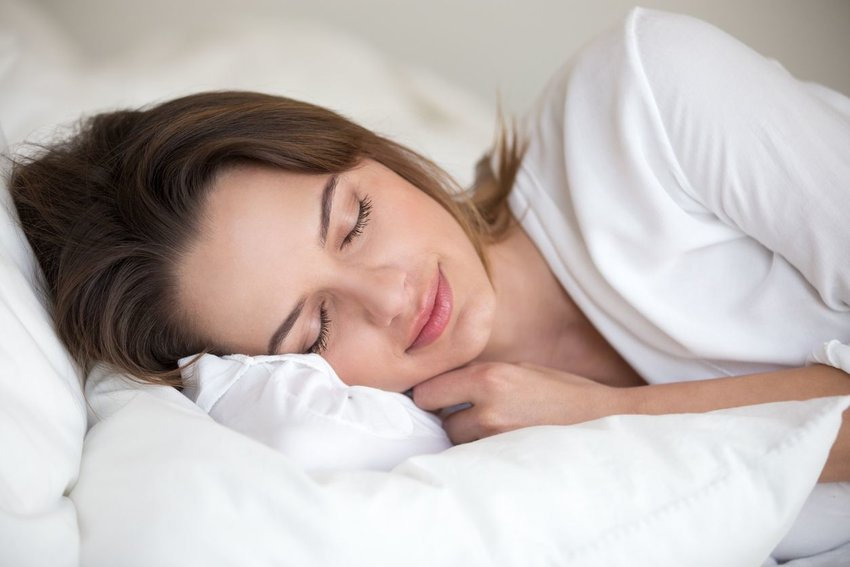 Woman sleeping peacefully on white sheets while wearing white shirt