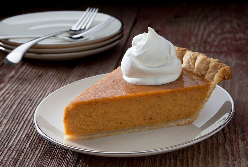 Slice of pumpkin pie with whipped topping plated on a rustic wooden table