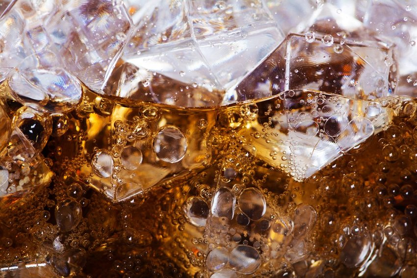 Up close view of glass of soda, with sparkling carbonation bubbles and ice cubes