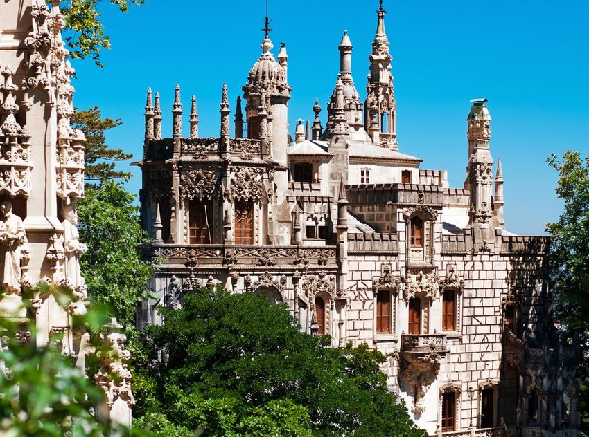 View of the modern Regaleira Estate castle and trees in Sintra, Portugal