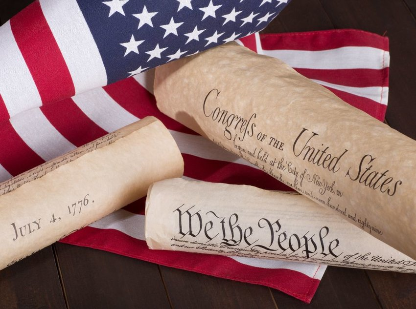 American historical documents including Bill of Rights set against patriotic American flag