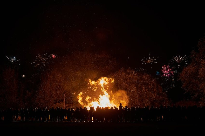Large crowd of people circle around huge bonfire with fireworks in background, lit at night