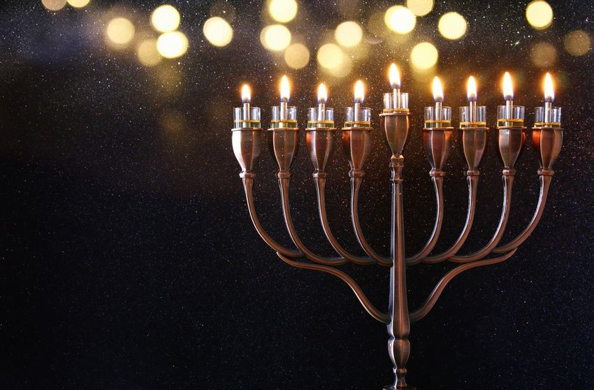 Traditional Jewish Menorah lit for holiday celebration against a black backdrop
