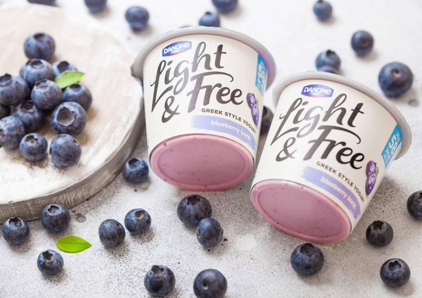 Yogurt cups with blueberries scattered on table, showing Danone logo on package