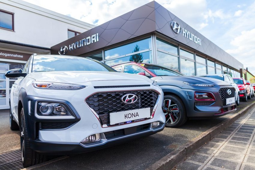Hyundai dealership showing new cars and company logos on a clear afternoon