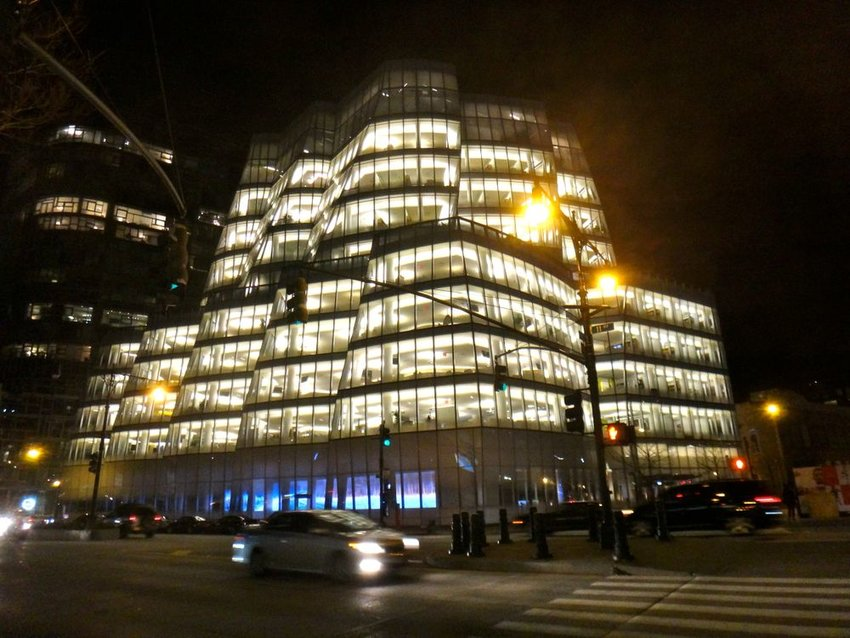 Night view of large IAC building architecture, lit from the inside with busy urban nightlife
