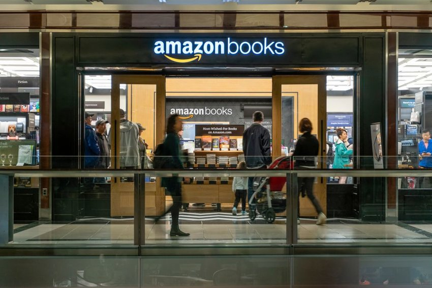 Busy people traveling in front of Amazon book store at night, New York, USA