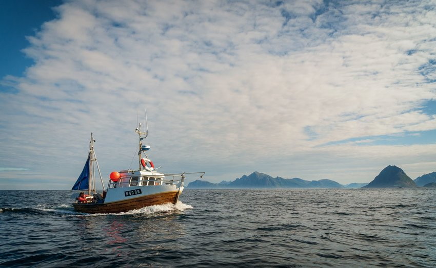 Commercial fishing boat on the ocean with mountains in the background