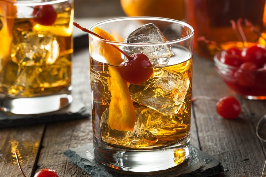 Old Fashioned cocktail with orange peel and cherries served in a clear glass