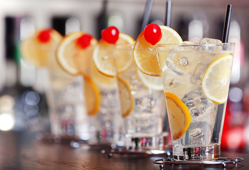 Row of traditional Tom Collins cocktails with lemon on a wooden bar