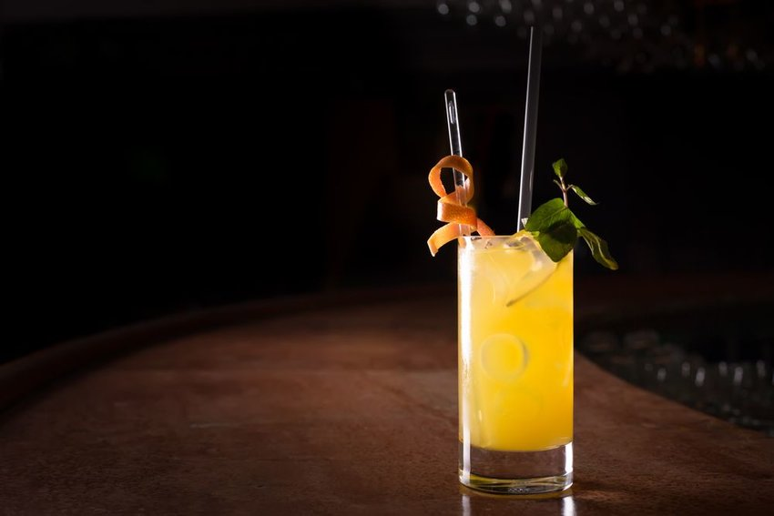 Fancy Screwdriver cockail with garnish in a dark bar