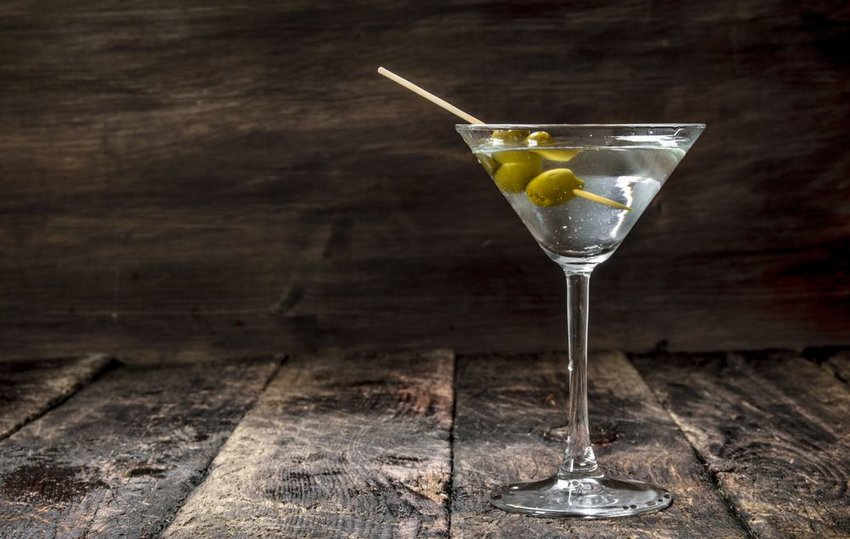 Traditional Martini with olives and toothpick on a wooden table