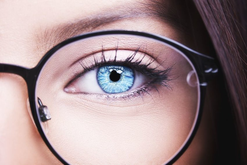Up close view of a woman's blue eye with large black eyeglasses frames