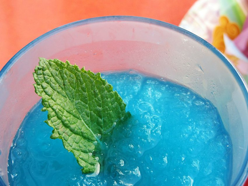 Up close view of blue slushie drink with crushed ice and mint leaf sticking out