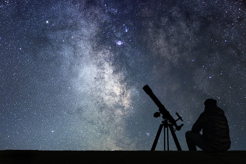 Man sitting with large telescope, silhouetted against a starry night sky