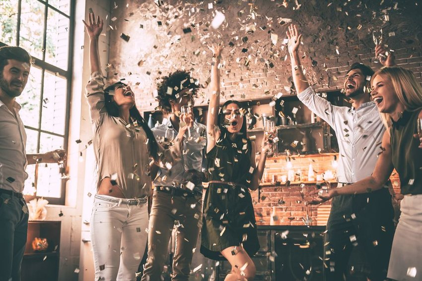 Celebratory group of people cheering and throwing confetti in the air