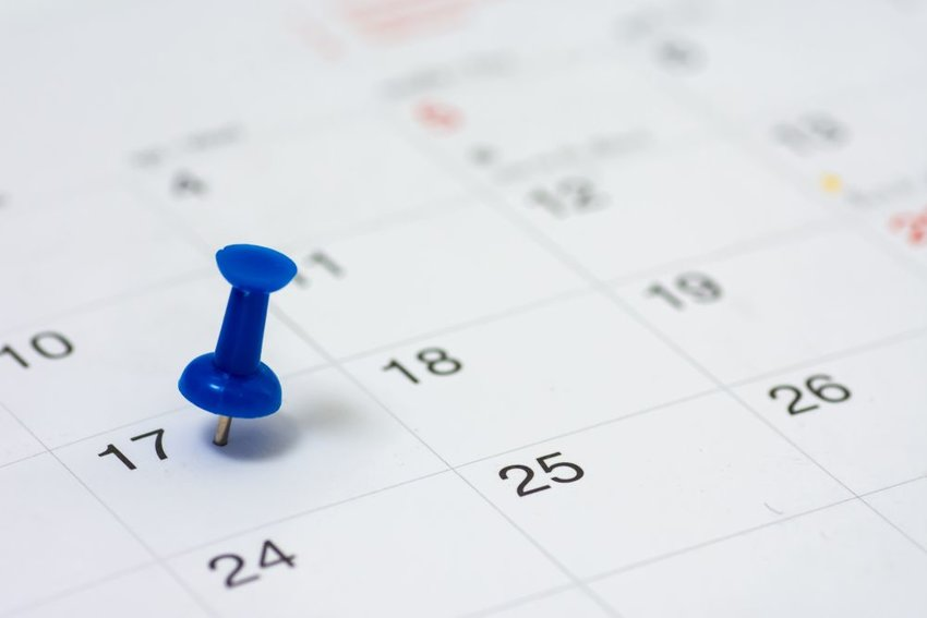 Up close view of monthly calendar with blue pushpin marking a day