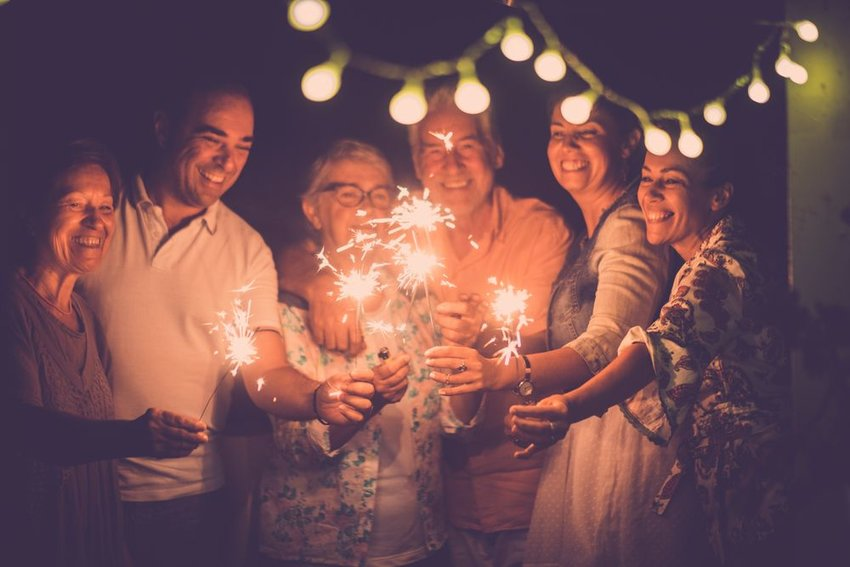 Group of people celebrating, standing in a circle and lighting sparklers at night