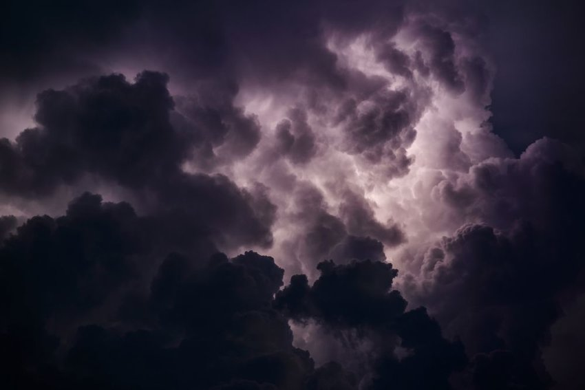 Sky view of dark and stormy thunderclouds illuminated by internal lightning flashes