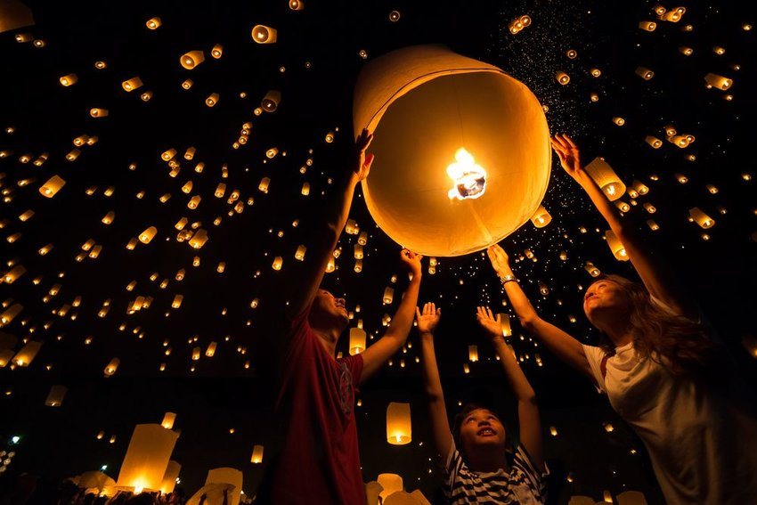 Group of people standing around paper lanterns, releasing numerous bright lamps into the sky
