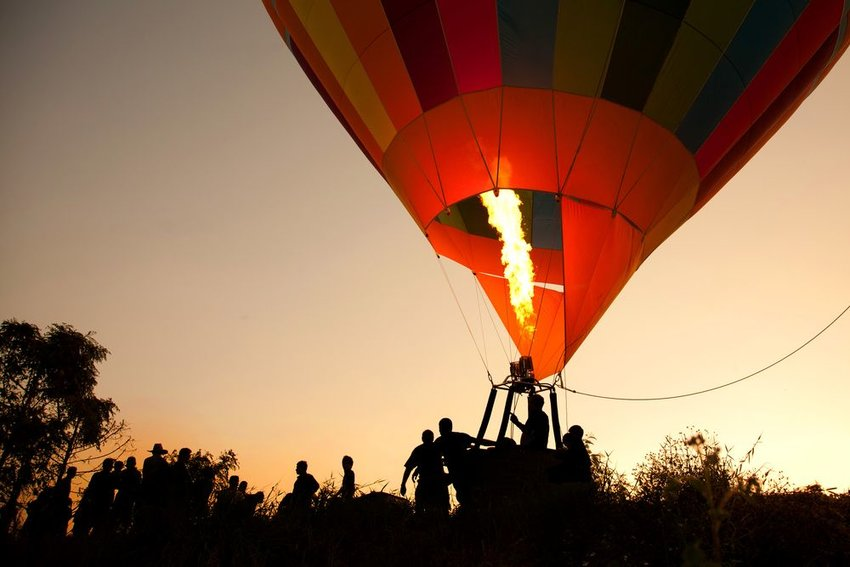 Silhouette of group standing and filing in to a hot air balloon passenger basket