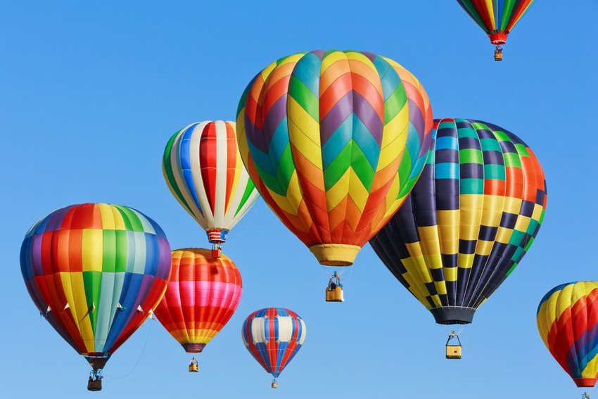 Assorted colorful hot air balloons moving through the air in a pack, set against blue skies