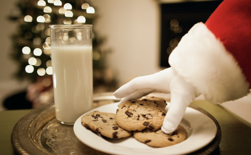 A gloved hand picking up a chocolate chip cookie with a glass of milk on the side