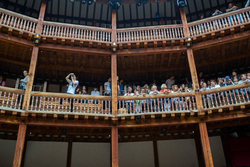Interior of the Globe Theater with people sitting on a balcony