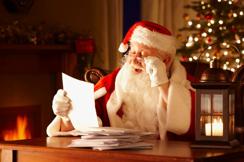Santa Claus reading list with fireplace on and Christmas tree in background