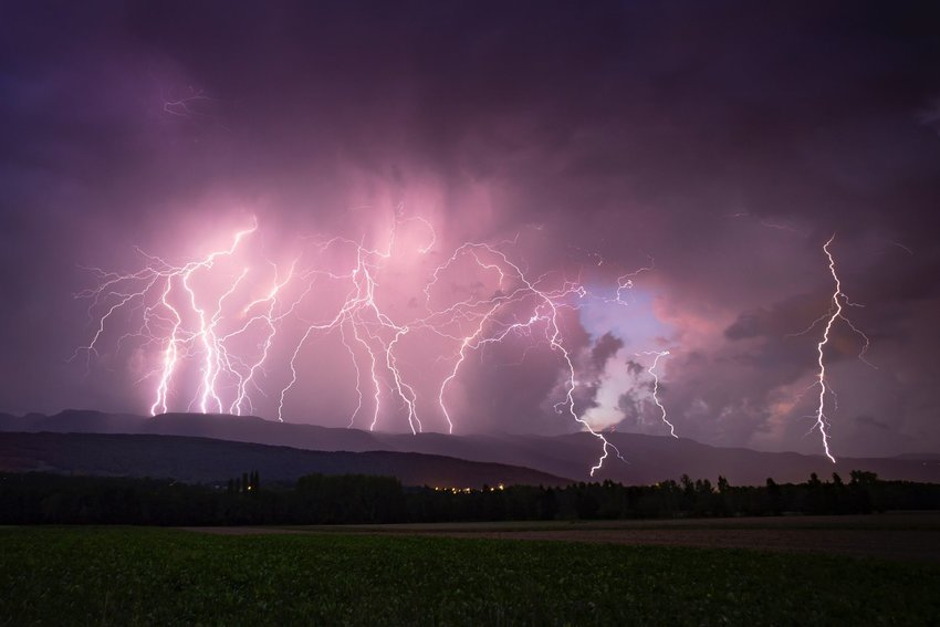 Lightning striking in multiple places on hilly landscape