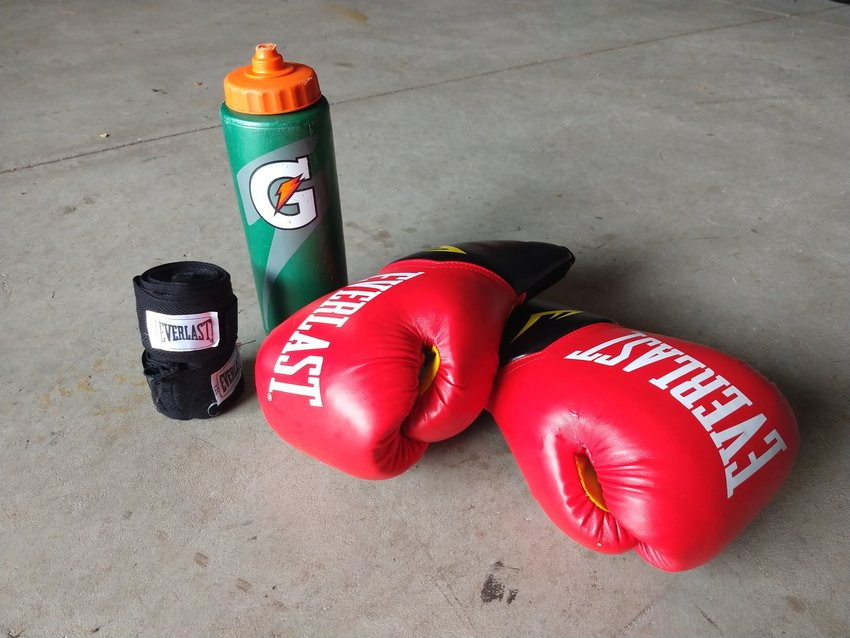 Pair of red boxing gloves with a reusable water bottle
